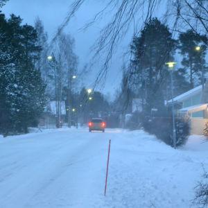 Snöstorm, bil kör på vägen, mycket snö, snön yr och blåser.