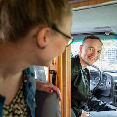 Jani Keto kurkkaa Anni Vilkkiä matkailuauton kuljettajan paikalta.