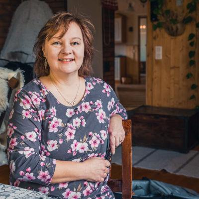 Kansanedustaja Anne Kalmari istuu kotona pöydän äärellä.