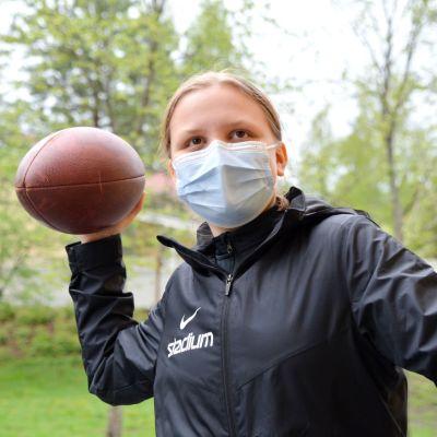 Julia Helppolainen i munskydd och svart jacka med en amerikansk fotboll i handen.