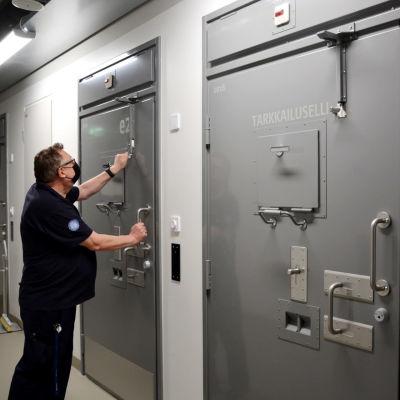 en man i skjorta, munskydd och glasögon låser upp flera lås till en fängelsecell, på bilden syns tre gråa dörrar till fängelseceller