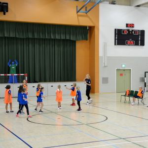 juniorer spelar handboll i en idrottshall.
