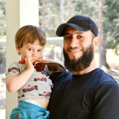 Adam Aki i grå t-skjorta med bilar på i famnen på Abdul Aki i svart t-skjorta och keps.