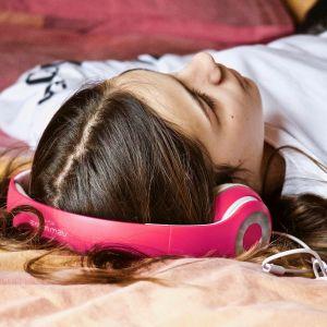 Nuori nainen kuuntelee kuulokkeilla