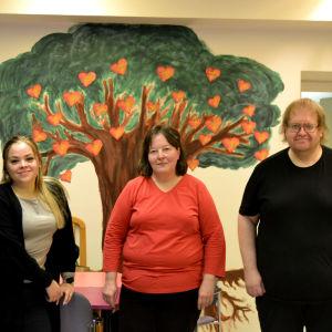 Tre människor står och tittar in i kameran, bakom dem en väggmålning av ett träd med hjärtan i grenarna.