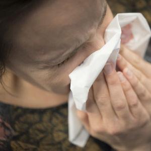 En kvinna snyter sig i en näsduk
