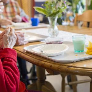 Matbord med använda kärl. Äldre personer sitter runt bordet.