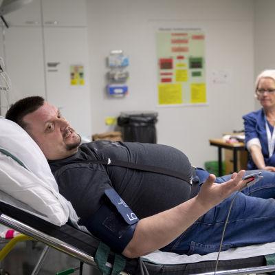 Man ligger på bår med någon apparat fastkopplad i fingret. I bakgrunden sitter en sjuksköterska.