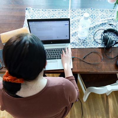 En person jobbar på sin laptop vid sitt matbord.