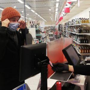 Kund tar av sig munskydd för att kunna identifieras av kassapersonal.