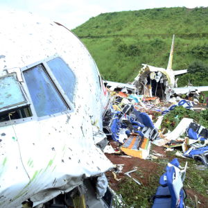Flygplanet som slitits itu. I förgrunden ser man nosen på ett flygplan som är smutsigt och trasigt. Längre bort i bakgrunden av bilden ser man änden av flygplanet. Mellan flygplansdelarna ser man allt innehåll i flygplanet som ligger utspritt på marken.
