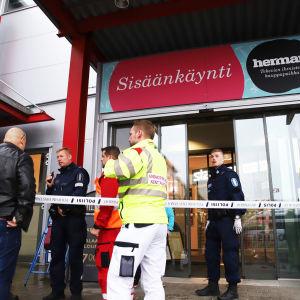 En av köpcentret Hermans ytterdörr. Utanför dörren syns räddningspersonal om en civilklädd person.