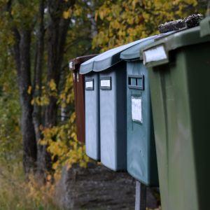 Postlådor på rad i ett lite ruskigt höstväder.