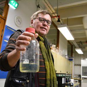 Jyri-Pekka Mikkola håller upp en flaska med det fossilfria bränslet, en klargul vätska, i ett laboratoriet.