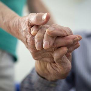 Två personer håller varandra i hand.