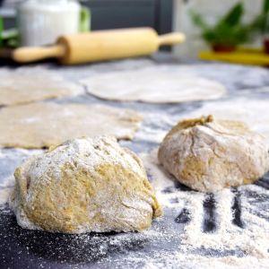Ett bakbord med några degklumpar, mjöl, och utkavlade tunnbröd. I bakgrunden en suddig kavel.