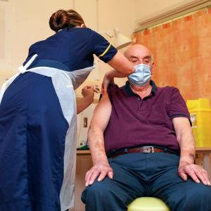 Bild på man i lila tskjorta. Mannen får vaccin av sjukskötare.