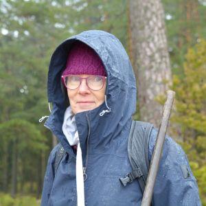 Päivi Kippo-Edlund i blå jacka med huva på i skogsmiljö i regnigt väder.
