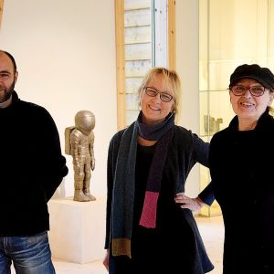 tre personer i svarta kläder i utställningsutrymme