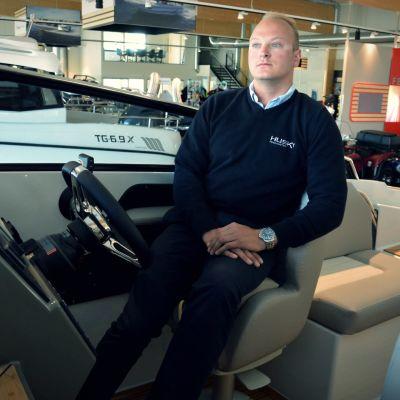 Roger Granfors i förarsätet på en motorbåt i en båtbutik.