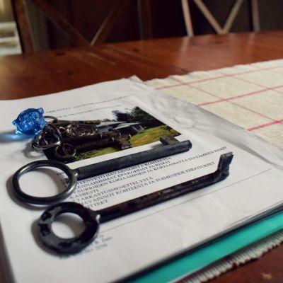 En nyckelknippe framlagd på ett bord i vardagsrummet på ett gammal hus. Husförsäljningspappren under nycklarna på bordet.
