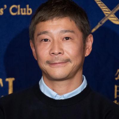 Yusaku Maezawa framför en blå skärm.