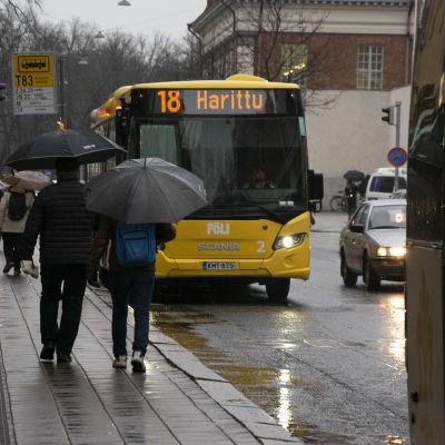 Ihmisiä ja linja-autoja Turun Linnankadulla.