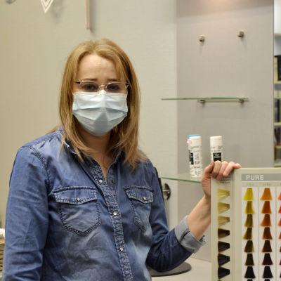 Kvinna med munskydd och glasögon står och håller i en färgkarta för hårfärger. Hon tittar rakt in i kameran.