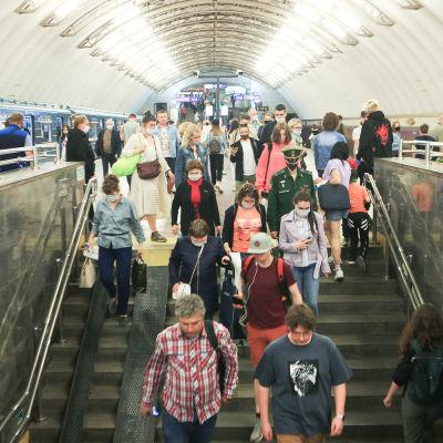 Människor går ner för trappan i S:t Petersburgs metro. De flesta bär munskydd.