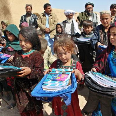 En grupp afghanska flyktingbarn visar upp sina skolväskor på ettflyktingläger i Pakistan.