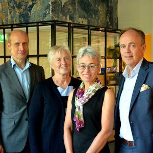 Jukka Sjösten, Clara Högnäs, Marita Waris och Henrik Karlsson står på rad och ler in i kameran.