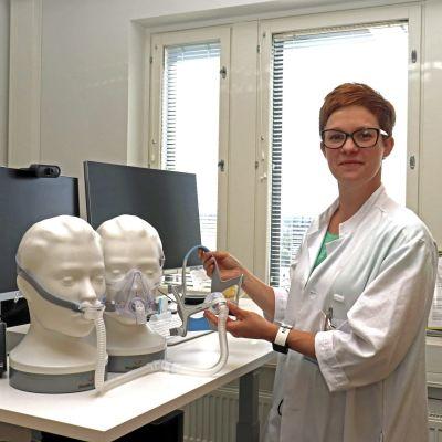 Apulaisylilääkäri Hannele Hasala esittelee uniapnean CPAP-hoidossa käytettäviä kasvomaskeja Tampereen yliopistollisessa sairaalassa 9. kesäkuuta 2021.
