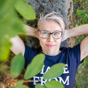 Varpu Marjomäki makaa kivisellä istuimella ja poseeraa kameralle.