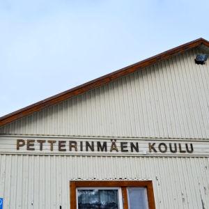 Närbild av en gammal träbyggnad, beige färg, det står Petterinmäen koulu på väggen.