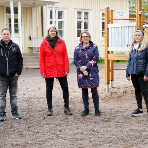 Fyra personer står framför en skolbyggnad.