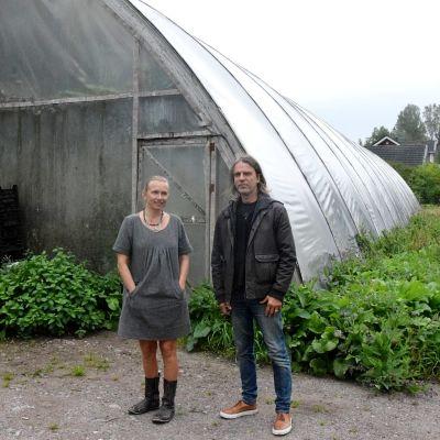 kvinna och man framför växthus
