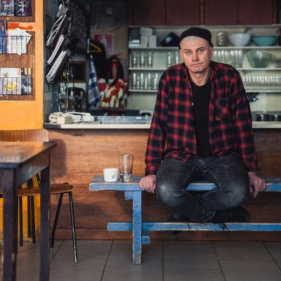 Vakiopaineen baarimikko Matti Perälä istuu jakkaralla ja katsoo kameraan.