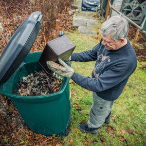 Mies kaataa biojätettä kompostiin omakotitalon pihalla.