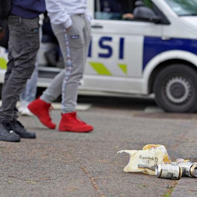 Ölburkar som ligger på marken framför ungdomar.