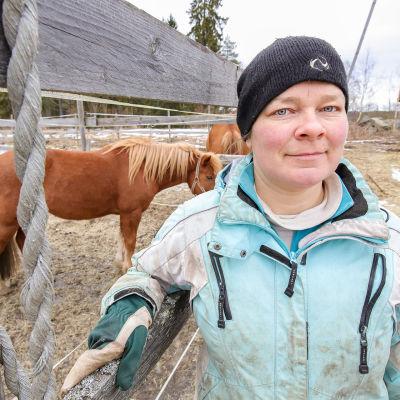 Riikka Jukola seisoo hevosaitauksen portilla.