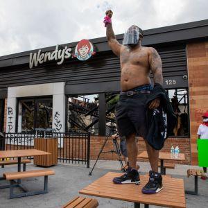 En man med bar överkropp står på ett bord utanför restaurangen Wendy's. Han har höjt näven i vädret.
