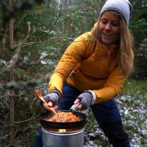 En kvinna med gul jacka och grå mössa lagar mat på ett stormkök i skogen.