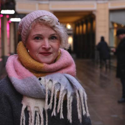 Kvinna med halsduk och stickad mössa som tittar rakt fram.