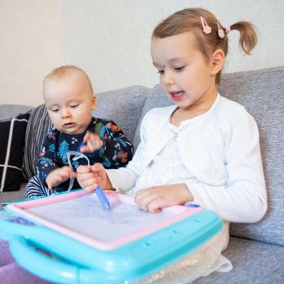 Esteri Kyrönlahti piirtää piirtolelulla Eetu -vauvan katsoessa vieressä.