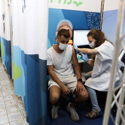 Sairaanhoitaja antaa kolmata koronarokoteannosta miehelle Israelissa.