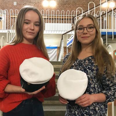 Ada Rantala (vas) ja Emilia Tammilehto valkolakit kädessä Lyseonpuiston lukion juhlasalissa.