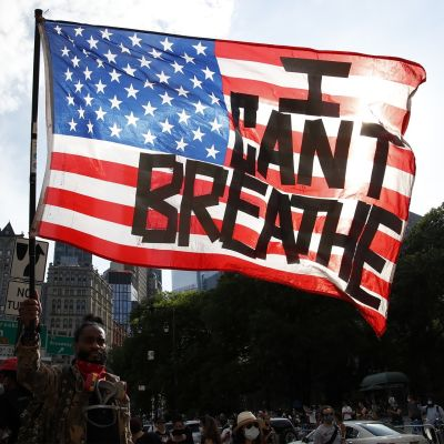 """Mielenosoittaja kantaa lippua, jossa lukee """"En pysty hengittämään"""""""