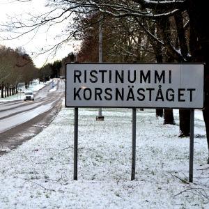 Vägskylt som det står Ristinummi Korsnäståget på. I bakgrunden kommer en bil körande. Det är lite snö på marken.