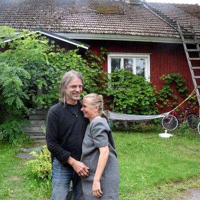man och kvinna på gårdsplan till rött trähus
