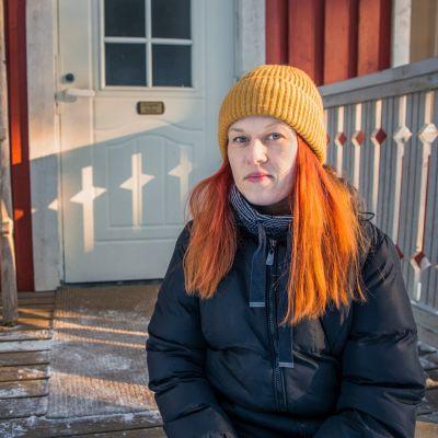 Anna Penttilä istuu hometalon kuistilla.